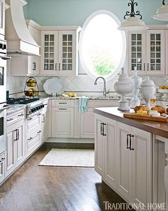 We're not sure what feature we like more, the oval window above the sink, or the robin's egg blue paint on the walls, but this spacious cottage kitchen exudes charm. Materials include a tile backsplash, granite counters, and a wood-topped island.