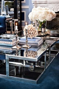 "A modern coffee table styled with an eclectic mix of books, coral, candle sticks and flowers makes a living room feel ""pulled together"" yet inviting. To find unique collection of decorative accessories along with beautiful coffee tables, furniture and lighting shop online at www.dashhomecollection.com"