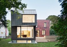 The street-facing elevation of this brick and steel extension to a 1920s Montreal property echoes the proportions of the original building, but at the rear a large angular outcrop projects over the back garden.