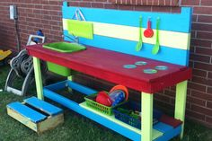 Outdoor Mud Pie Kitchen. Our kiddos love this! My husband and father-in-law built it from scrap wood my uncle was throwing out. We drilled a hole in a plastic tub for the sink and ran an old kitchen faucet to the water hose spout. The stove top burners are CD's wood glued to the top. Lots of muddy fun!!