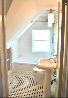 Small bathroom in converted attic space. Like their shower solution.