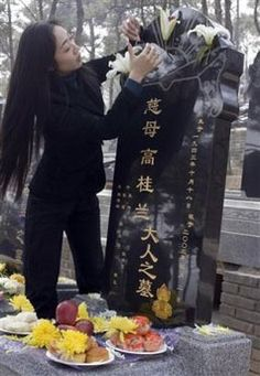 Dressing a grave w/flowers and food; Beijing; annual Tomb Sweeping Festival, Qing Ming