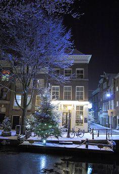 Cafe Amsterdam en un canal en una noche nevada