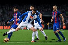 Lionel Messi (L) of FC Barcelona and Andres Iniesta of FC Barcelona competes for the ball with RCD Espanyol players during the La Liga match between FC Barcelona and RCD Espanyol at the Camp Nou stadium on December 18, 2016 in Barcelona, Catalonia.