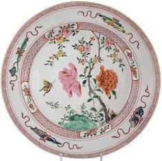 Très grand plat peint dans les émaux de la famille rose en porcelaine de Chine de la Compagnie des Indes d'époque Yongzheng Plat en porcelaine, richement peint dans des émaux « Rose-Vert », décoré sur le bassin d'un tertre rocheux peint dans des émaux verts sur lequel naît un prunus et deux importantes branches de pivoines en fleurs,