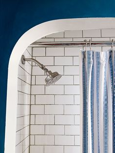 White subway tile with dark-gray grout adds textural interest to this teal-blue bathroom.