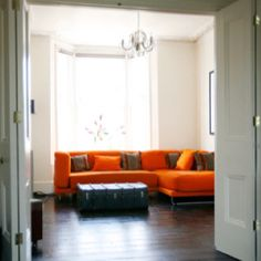 Neat living room.  I wonder if we could reapholster our neutral couch to a more fun color.