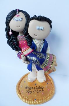 Bright pink  Royal blue is the colour scheme for this lovely couple from the USA! I make anything you want, any outfits. Custom handmade to look like you, I send my work anywhere in the World. A couple like this is £149.99, a base is £9.99, you can see more of my work at www.indian-wedding-cake-toppers.com (shows my Asian/Indian/Pakistani toppers) www.googlygifts.co.uk shows all my work.