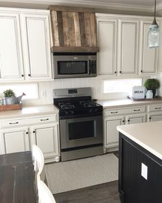 "Lauritzen Home Projects. Glued beadboard to existing tile backsplash with construction adhesive. $40 fix!   Added ""bun feet"" to cabinets and made a faux oven hood out of pallet wood to reach farmhouse look. Was completely builder grade kitchen before-honey oak cabinets, floor tile for backsplash, etc."