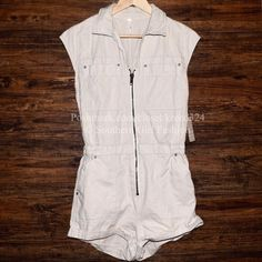 FREE PEOPLE Romper Zip Up Onesie Utility Jumpsuit Size XS. New with tags. $128 Retail + Tax.   Zip-front utility romper with rolled bottom, featuring hip, back, and breast pockets.  Elastic smocking around back of waistband.  Color looks gray/cream.   100% Cotton.  Imported.     ❗️ No trades.   Bundle 2+ items for a 20% discount!    Stop by my closet for even more items from this brand!  ✔️ Items are priced to sell, however reasonable offers will be considered when submitted using the blue…