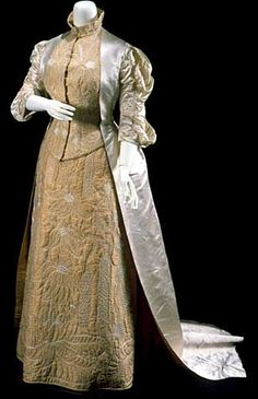"""1881 Wedding dress of ecru silk satin with elbow-length sleeves and a long overskirt panel which ends in a train. The sleeveless bodice and cylindrical skirt are hand quilted with a variety of floral images that Jane Grey Swisshelm reports are """"from memory of a visit to Eagle's Nest Lake in Sherburne County ."""" Worn by Zoe Swisshelm, daughter of Jane Grey Swisshelm, abolitionist and advocate of women's rights."""