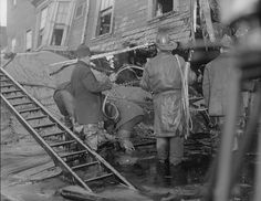 Boston Molasses Disaster of 1919 -- Firemen standing in thick molasses after the disaster. Muck drips off the ladder's rungs.