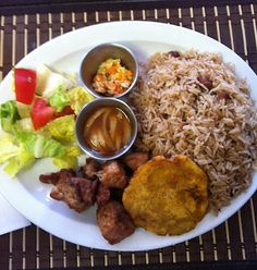 Fried pork, red beans rice, salad and plantains - Haitian food