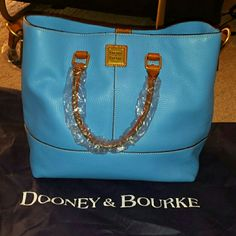 "BRAND NEW Dooney & Bourke Dillen Leather Handbag BRAND NEW.  Color is Aegean Blue.  North/south design. 5"" double handles. Adjustable shoulder strap. Middle zipper compartment.   12-1/2""W x 12""H x 6-1/4""D.  100% genuine leather. Comes with a dustbag. Dooney & Bourke Bags"