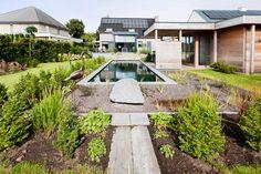 zwemvijver met Belgische blauwe hardsteen afgewerkt en een geïntegreerd poolhouse