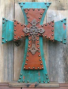 could make this with various sized wooden crosses, paint and upholstery tacks with ornate cross on top