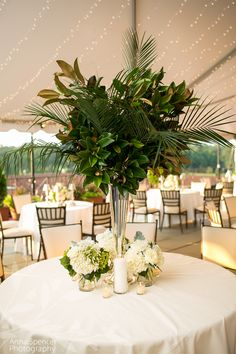 Tall greenery based centerpiece with magnolia leaves and low white floral arrangements at a tent wedding reception. Britt Wood Designs florist.