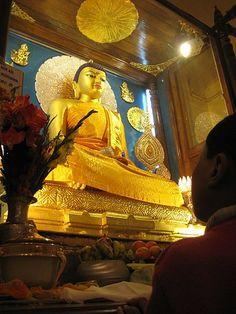 Egy buddhista gyakorló teszi tiszteletét Buddha előtt a templomnál.