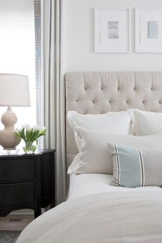 A black French nightstand topped with a beige double gourd lamp sits in front of a window dressed in white, blue, and gray curtains.