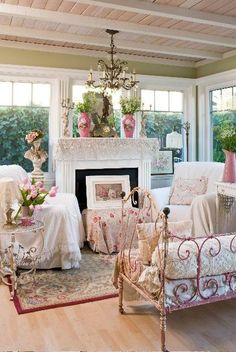 rose-colored wrought iron couch. shabby chairs flank fireplace.