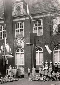 Weeshuizen. Hoekje van de speelplaats van het Burger Weeshuis aan de Goudsche Wagenstraat in Rotterdam. De grotere weesmeisjes dragen de typische weeskinderenkleding [met een witte schouderdoek en een dito kapje]. Foto 1923.