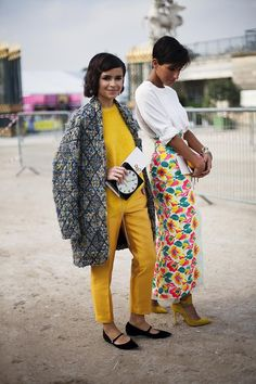 Miroslava Duma in a grey cardigan + mustard yellow cashmere sweater + mustard yellow trousers + black ballet flats; white tee + floral bromide red skirt + yellow suede ankle-strap heels