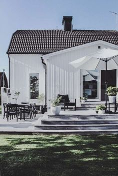 Summer style with Black, white and green! Love the farmhouse look with the decks, umbrella and lots of seating!