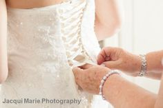 Lacing the bride's wedding dress - by Hampshire wedding photographers Jacqui Marie Photography. VISIT http://jacqui-marie-photography.co.uk for details