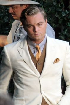 Gatsby in cream suit, tan vest and ORANGE neck tie... also pale blue shirt...