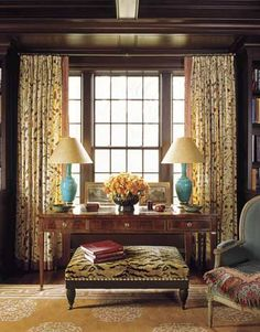 """Since a mahogany-paneled library can tend to be dark, Roberts says, """"almost everything was chosen for its ability to pop,"""" including the Tibetan rug, curtains in Pierre Frey's L'Incourt, ottoman upholstered in Tiger Velvet from Brunschwig & Fils, and 1920s French vases mounted as lamps. The Swedish Neoclassical writing table is from H.M. Luther. Eric Piasecki  - HouseBeautiful.com"""