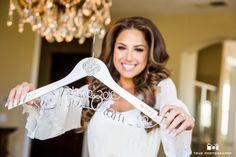 Bride holds up personalized hanger for wedding dress #weddingphotography / national wedding photographers