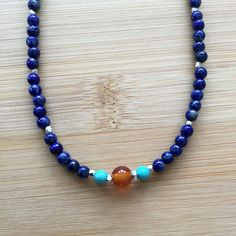 Lapis lazuli beads, interspersed with Karen Hill Tribe beads, links to a sterling silver curb-style chain. The center is highlighted with a large carnelian bead and two turquoise beads. The necklace fastens with a sterling silver spring clasp, adorned with a lapis bead. The
