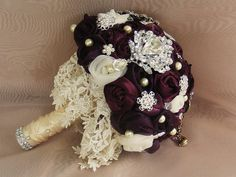 The bouquet has been made entirely from scratch,with aubergine purple and ivory organza and chiffon rosettes.  Color - cream,ivory,plum,aubergine purple