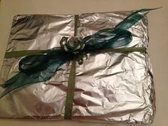 """Tenth anniversary is the """"Tin"""" or aluminum anniversary. I wrapped the gift in aluminum foil and them made an aluminum foil rose to add to the ribbon. So fun!"""