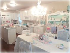 This is a kitchen, but if I had a dream craft room it would be all white with touches of turquoisy/aqua like this.  And a chandelier!