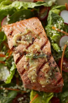 grilled fish on a bed of mixed greens