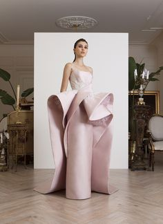 Strapless, light pink, double satin gown, with sculputral volumes on waist, that extend to the back in the form of a train,with thread embroidery motifs and off-white goldwork.