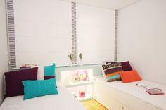 """Neste quarto de 12 m² compartilhado por duas irmãs, uma cabeceira com dois nichos embutidos entre a cama faz as vezes de criado-mudo. """"Escolhemos branco para os revestimentos, com detalhes em verde e lilás"""", explicam a arquiteta Juliana Bianchi e a designer de interiores Amanda Lima. O projeto foi feito em São Paulo."""