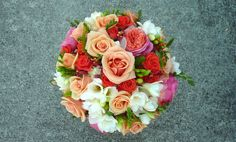 Stunning 'Peach Peony' 'Primadonna' and 'Springtime' roses blend beautifully with soft garden bits and fragrant freesia in this romantic garden bouquet