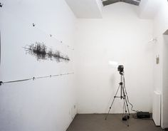 """Tim Knowles, """"Trans-Alp Project,"""" from the """"Vehicle Motion Drawings"""" series, installation view Zero Gallery. The drawing generated by the car's movements is made onto a roll of slowly moving paper recording the journey's twists and turns, starts and stops. The act of delivering the work to the gallery produces the work."""