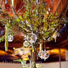 Leafy tree branches dressed up with flowers and hanging glass balls bring the outdoors in. I can't seem to get enough of these tree centerpieces!!
