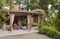 terrasse moderne avec pergola en bous et rideaux taupe, et une cheminée extérieure habillée de briques