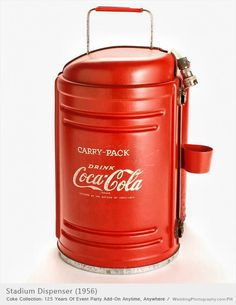 Red metal carry-pack dispenser with attached dixie cup holder that held 50 cups. The insulating plastic in this dispenser kept Coke cold for at least two hours.