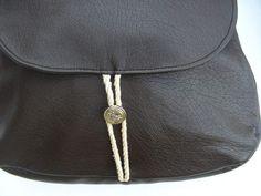 Ce sac besace est en skaï ou simili-cuir marron foncé, avec une forme évasée vers le bas. La doublure intérieure est en coton quadrillé marron et blanc (voir photo). Il possède une poche intérieure de 22 x 13 cm et 2 petites attaches en tissu pour accrocher...