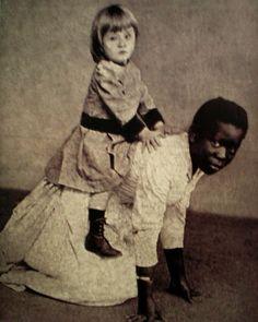 """Escrava brasileira serve de """"cavalinho"""" para criança branca. Esta fotografia, datada do final do século XIX, tem uma carga simbólica imensa e pode ser relacionada com inúmeros eventos violentos ocorridos no Brasil durante os séculos posteriores."""