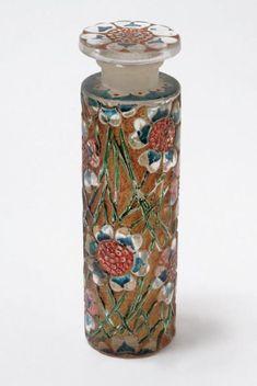 RENÉ LALIQUE - FORVIL « flacon tube fleur » Flacon en verre blanc soufflé moulé décoré en relief de fleurs. Bouchon moulé pressé de forme casquette décoré à l'identique, (bloqué). Signé sous la base « R. Lalique » Période 1924.