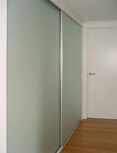 Armario empotrado a medida con interior de madera natural lacado en blanco y puertas correderas con esmalte vidriado y perfilería de aluminio anodizado