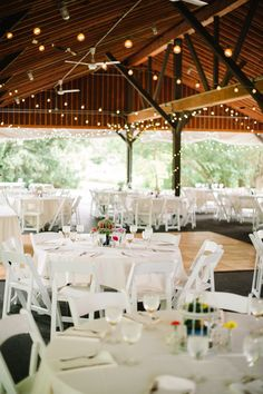 Outdoor reception under the pavilion, lovely white lights and white tables/chairs with pops of color from centerpieces