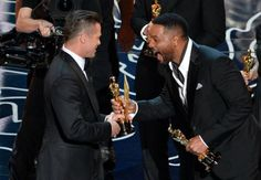 """Actor-producer Brad Pitt, left,  accepts the best picture Oscar for historic biopic \""""12 Years a Slave\"""" from actor Will Smith."""