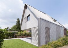 This gabled extension to a brick house in the Netherlands was designed to mimic the shape of the original property but is clad in an entirely different material.